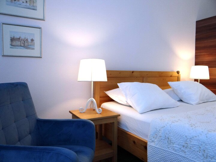 [:en]wooden bed, white pillows, sheets,blue chair, paintings,lamps,white wall[:]